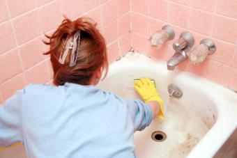 Woman scrubbing dirty bathtub
