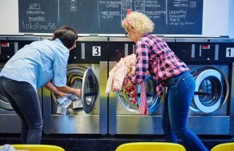 women inserting laundry into washing machines