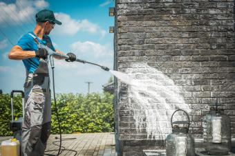 man using pressure washer to clean exterior brick wall