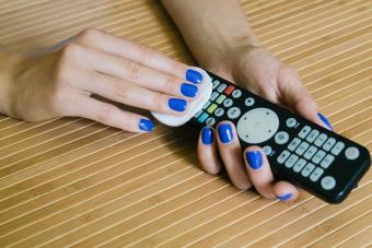 woman cleaning a remote control with a pad