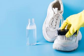 woman wearing rubber gloves cleaning salt stains from white sneakers with a brush.