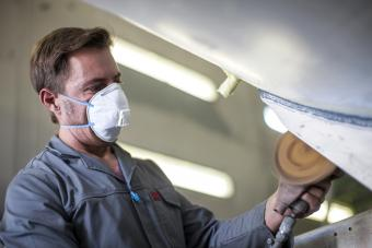 Industrial worker wearing protective mask while cleaning metal
