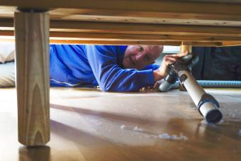 A man vacuums dust under a bed in an apartment