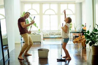 Father and daughter having fun mopping the floors