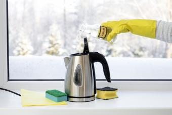 Pouring distilled white vinegar in a coffee pot