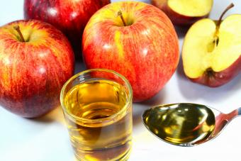 Apple cider vinegar in a cup and spoon with red apples on the background
