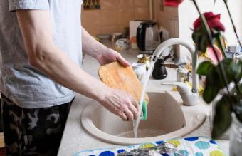 man washing cutting board