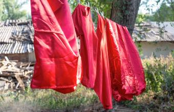 red silk bedding hanging outside