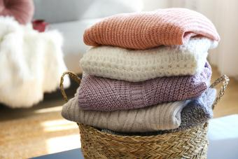 Pile of knitted sweaters of different colors and patterns perfectly stacked