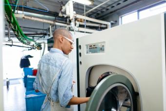 Young woman putting clothes into dry cleaning machine