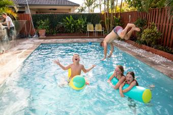 family plays in swimming pool