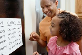 African father and daughter looking at chores chart
