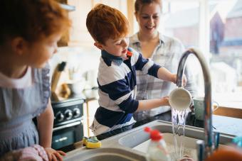 Two children and their Mother washing the dishes