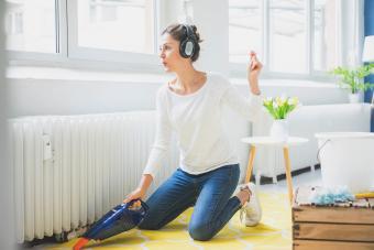 Woman at home wearing headphones hoovering the floor
