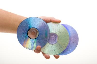 Hand holding several compact discs