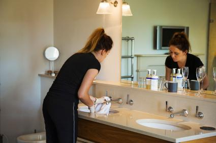 Standing woman cleaning sink