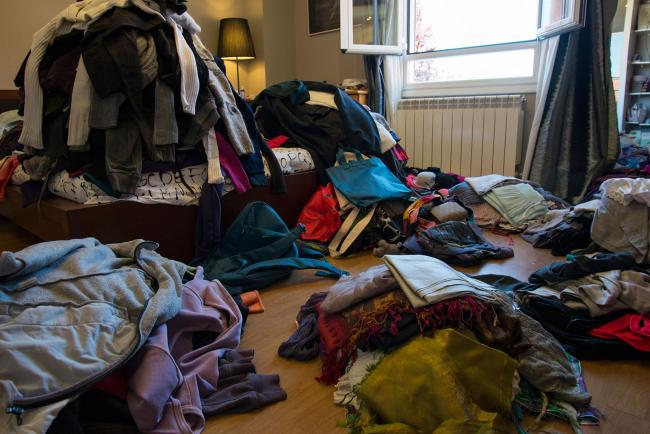 Clothes in a bedroom in piles