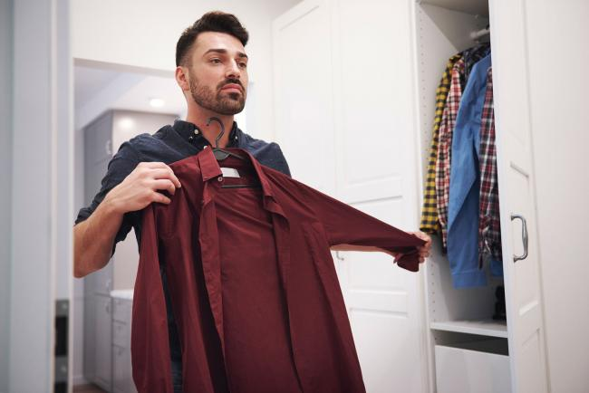 Man holding up burgundy shirt