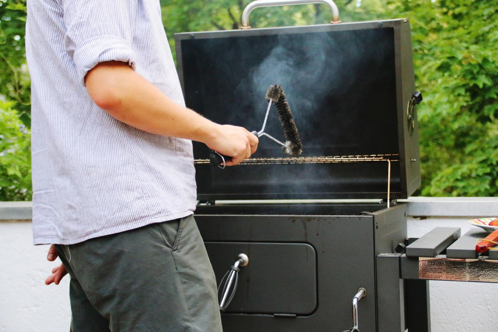 Man Cleaning Barbecue Grill With Wire Brush