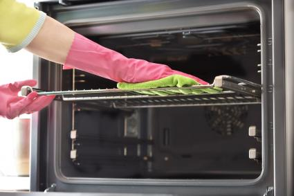 Woman with cleaning gloves cleans the oven racks