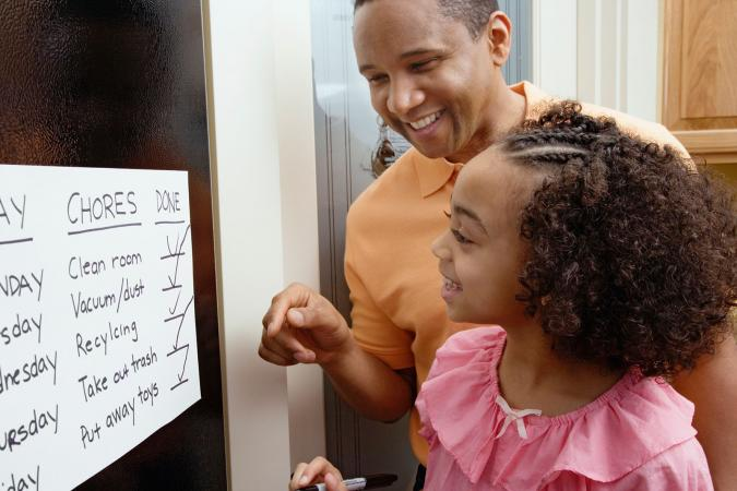 Father and daughter looking at chores chart