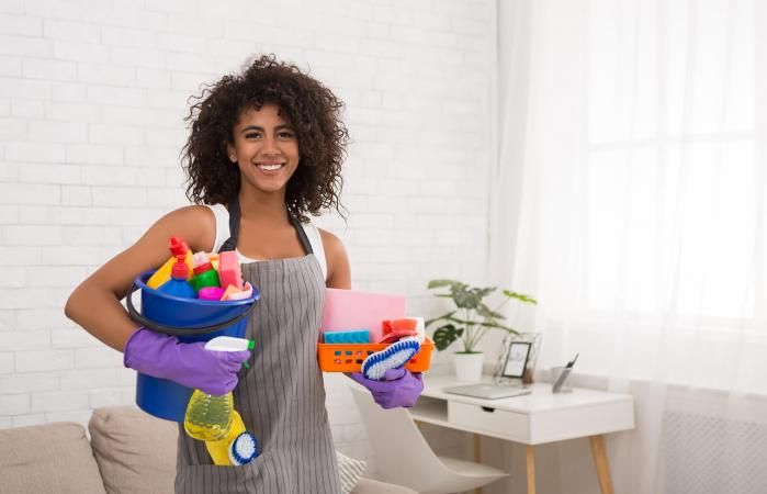woman posing with cleaning supplies