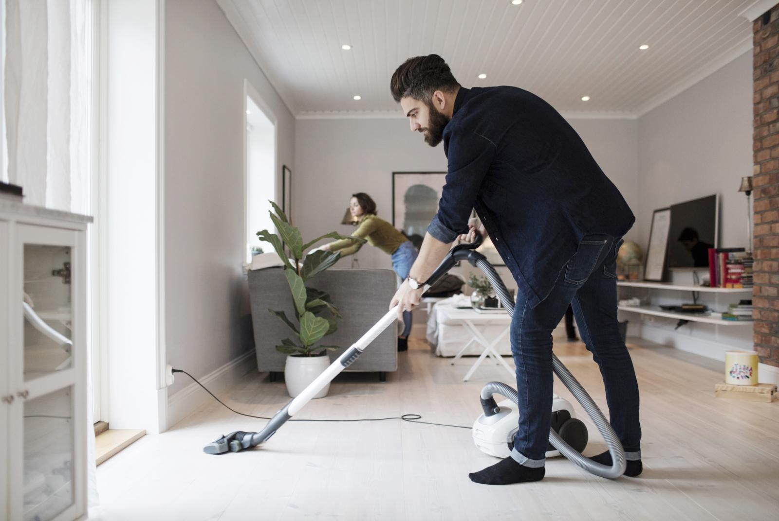 Man vacuuming floor while woman is cleaning
