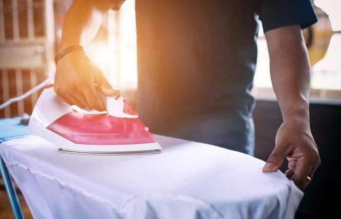 Man Ironing Shirt At Home