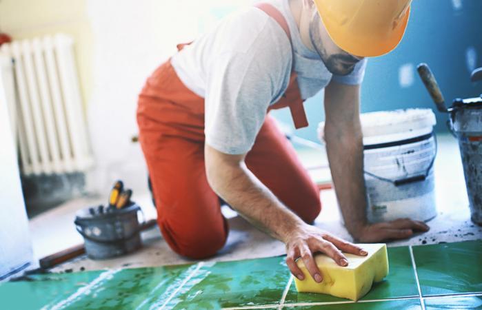 Handyman installing ceramic tiles