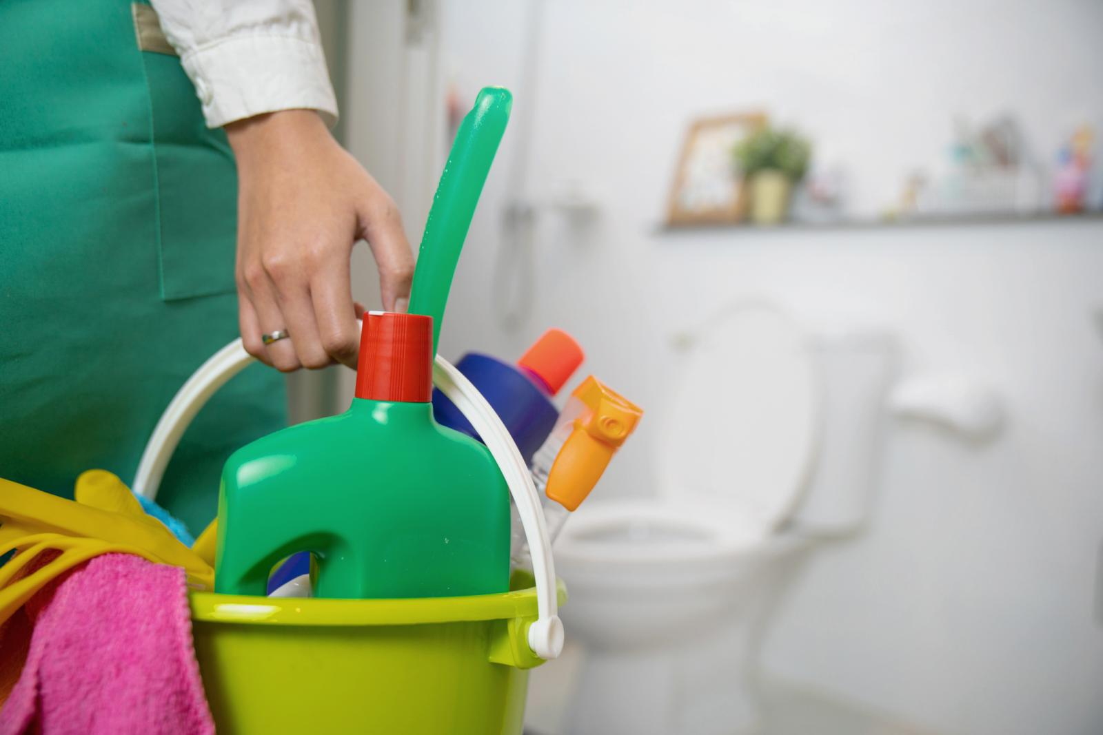 Woman is standing in the bathroom holding a bucket full of cleaning supplies