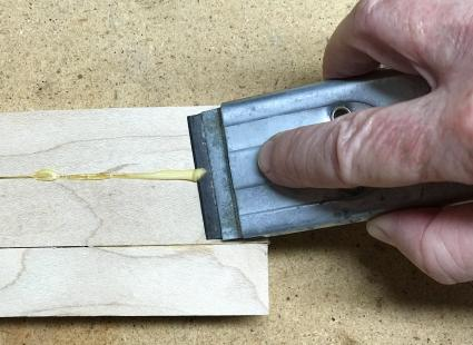 Scrape glue off wood with blade