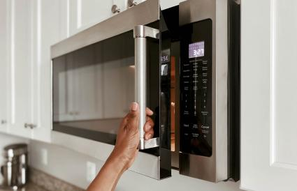 Woman opening a microwave oven