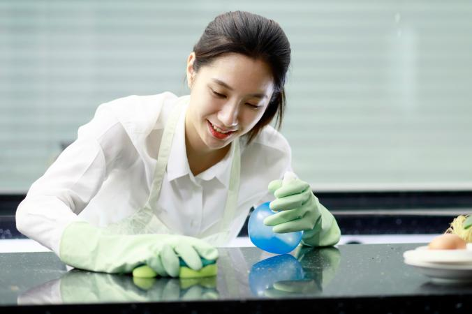 Woman disinfecting counter with bleach solution