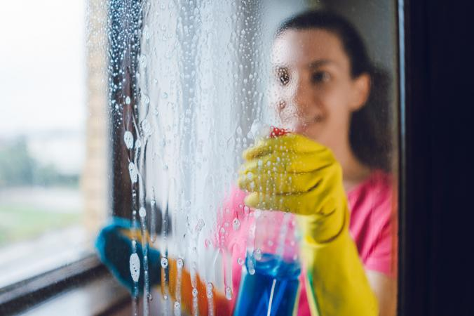 Woman spraying glass cleaner on window
