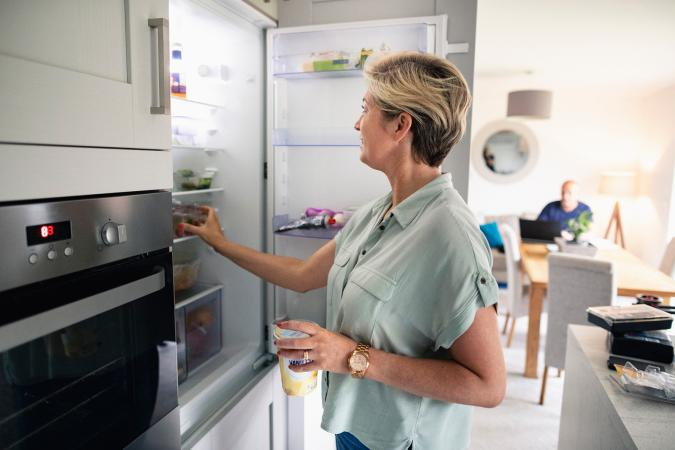 Woman putting food in refrigerator