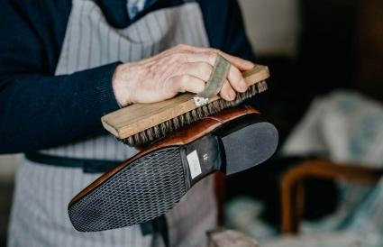 Old shoemaker is polishing a shoe