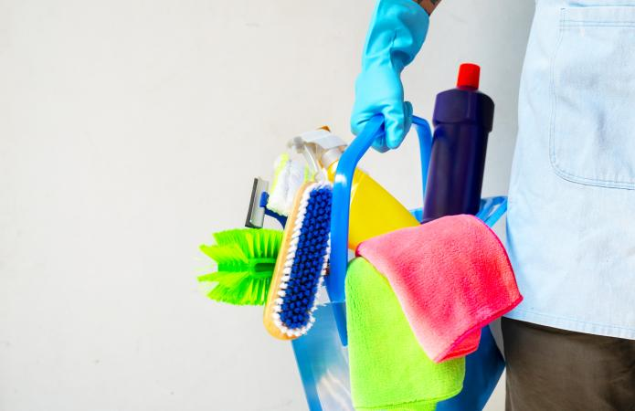 Man holding mop and plastic bucket with brushes, gloves and detergents