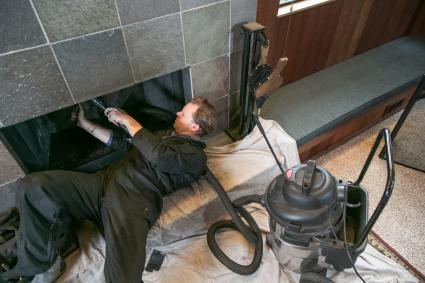 Chimney sweep cleaning chimney with soot vacuum