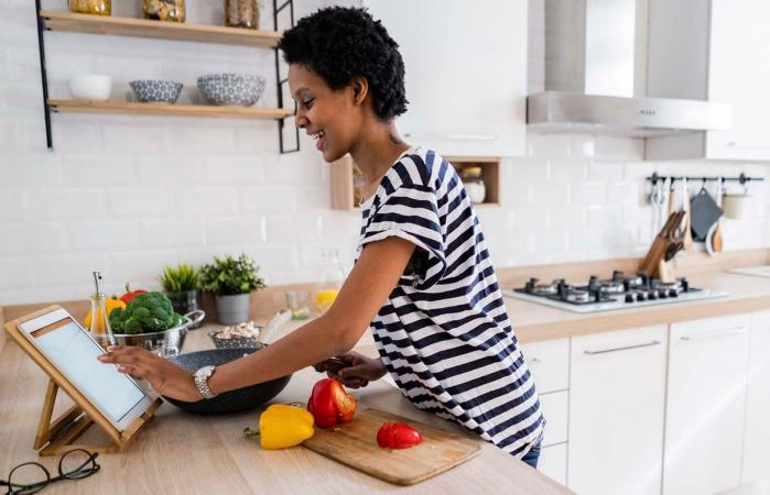 woman using tablet cooking in kitchen at home