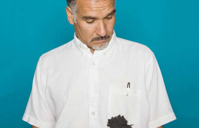 Man looking at ink stain on shirt