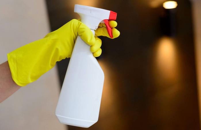 Hand holding detergent spray bottle