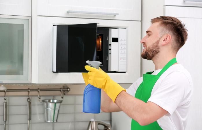 man cleaning microwave oven