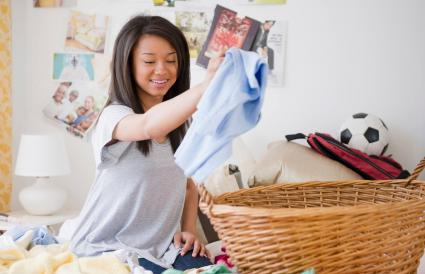 teenage girl doing laundry on bed