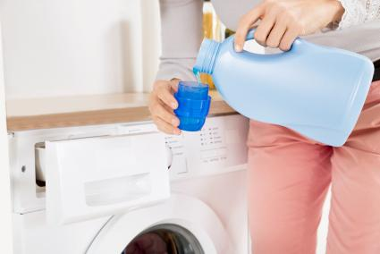 Female Hands Pouring Detergent In The Bottle Cap