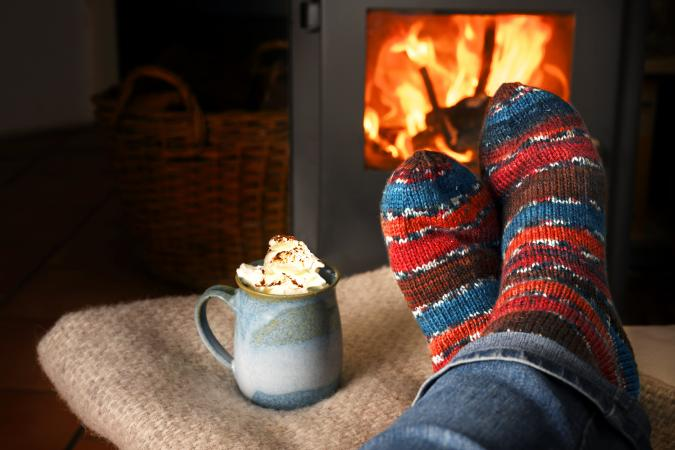 Person hearing wool socks against fireplace