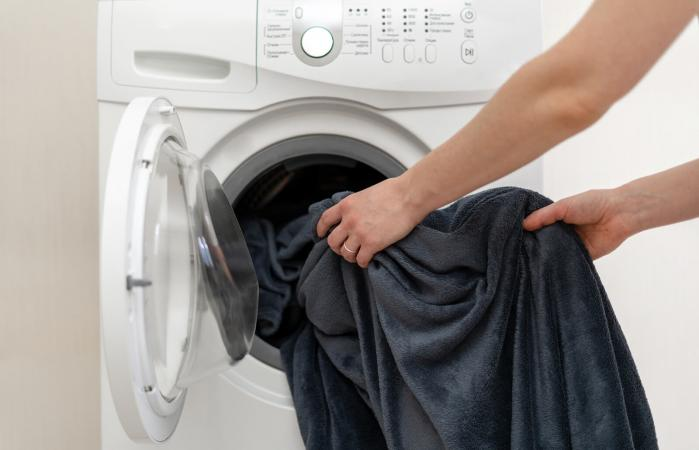 Woman putting blanket in washing machine
