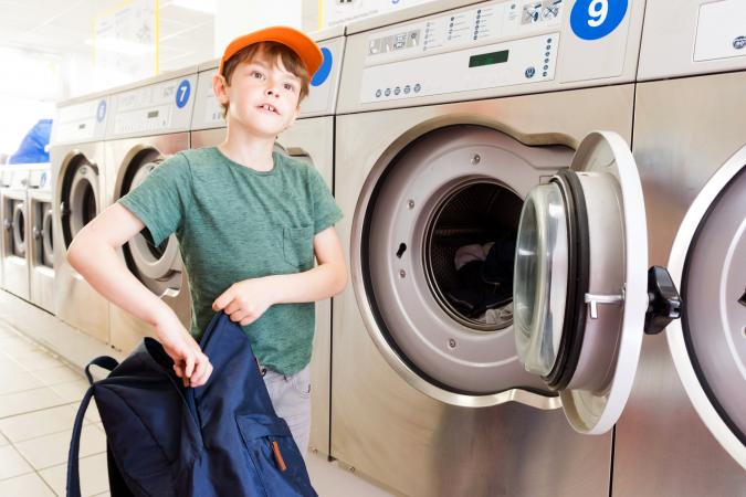 Boy Washing is backpack with a washing machine