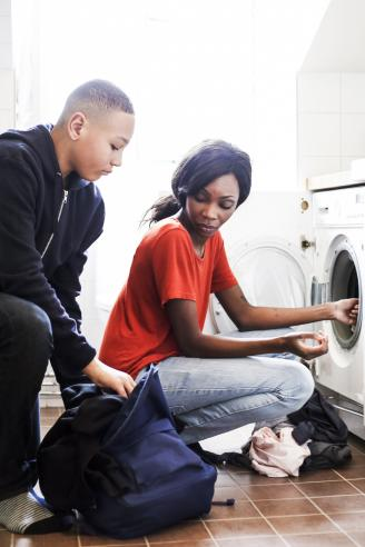 Teenage boy removing clothes from backpack while mother doing laundry