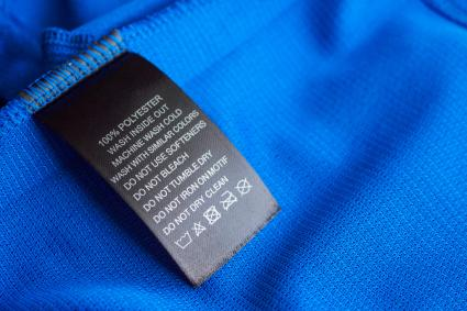 Laundry care washing instructions clothes label on blue jersey polyester