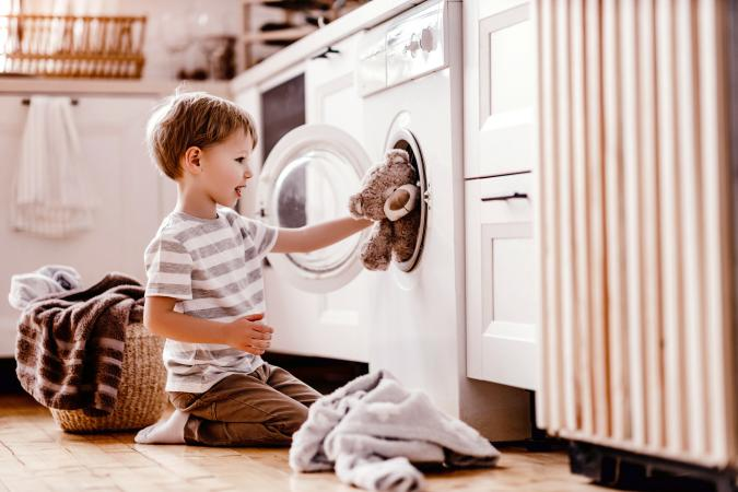 Boy in laundry with washing machine and teddy bear